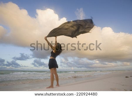 Hispanic woman holding flowing scarf on beach - stock photo