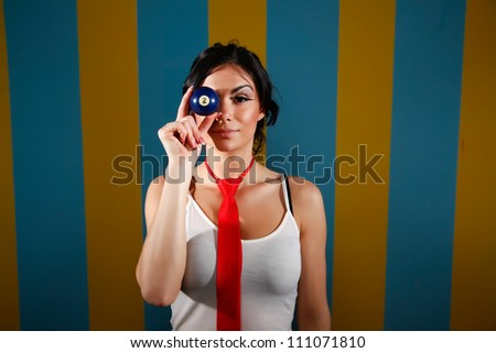 Hispanic woman holds an apple up to her eye. - stock photo