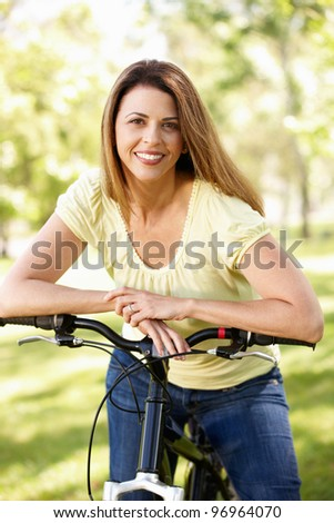 Hispanic woman in park with bike - stock photo