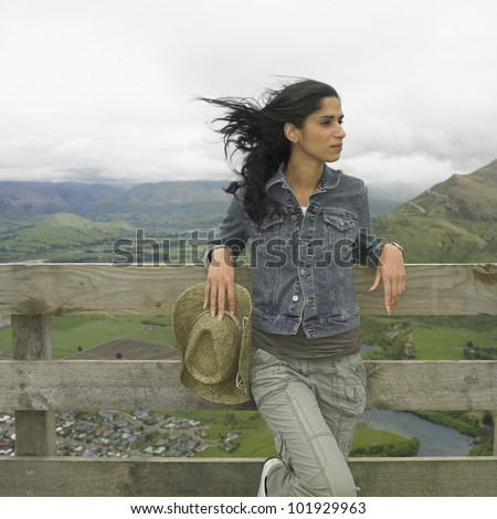Hispanic woman leaning on fence
