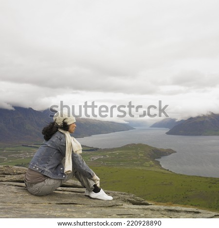 Hispanic woman looking out over water - stock photo