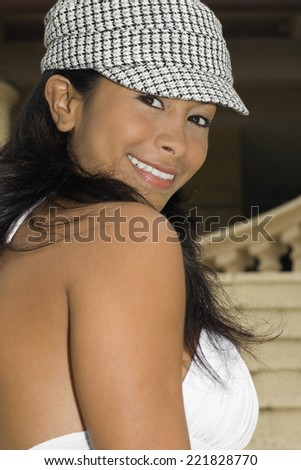 Hispanic woman looking over shoulder - stock photo