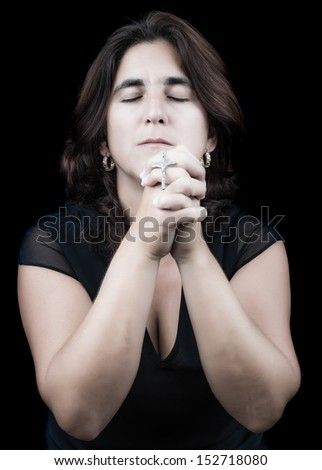 Hispanic woman praying with her eyes closed and holding a small crucifix (isolated on black) - stock photo