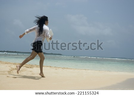 Hispanic woman running on beach - stock photo
