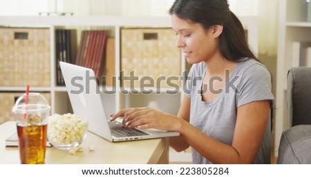 Hispanic woman using laptop on coffee table - stock photo