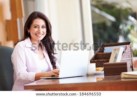 Hispanic Woman Using Laptop On Desk At Home - stock photo