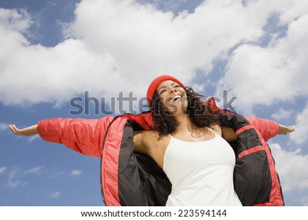 Hispanic woman with arms outstretched - stock photo