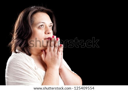 Hispanic woman with her hands folded in prayer and eyes open against a black background with space for custom text - stock photo