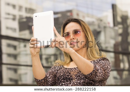 Hispanic woman with tablet outdoors wearing sunglasses posing for selfie