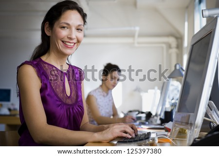 Hispanic woman working on computer at her desk