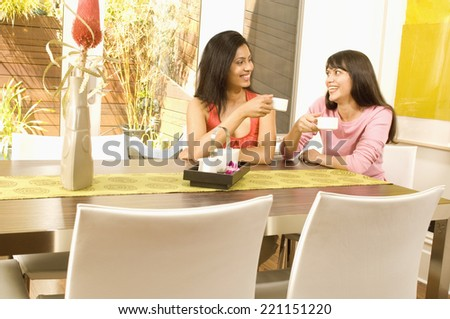 Hispanic women drinking coffee - stock photo