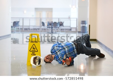 Hispanic worker falling on wet floor crying in pain