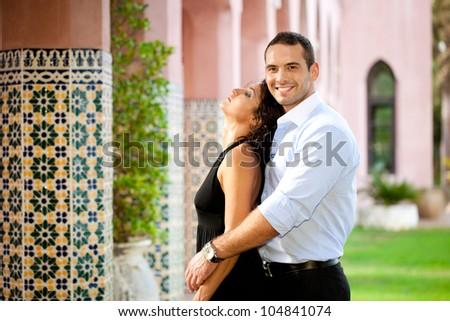 Hispanic young adult couple hugging outdoors - stock photo