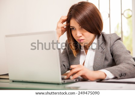 Hispanic young business woman looking upset and concentrating on her work in a laptop computer