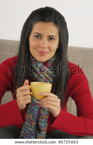Hispanic young woman drinking coffee or tea at home. - stock photo