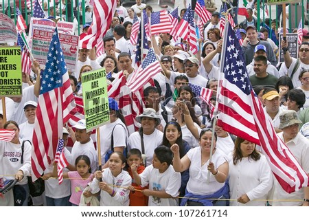 Hispanics wave American flags as immigrants participate in march for Immigrants and Mexicans protesting against Illegal Immigration reform by U.S. Congress, Los Angeles, CA, May 1, 2006 - stock photo
