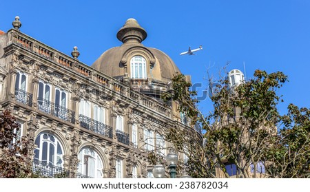 Historic building in downtown Porto with a plane flying through. - stock photo