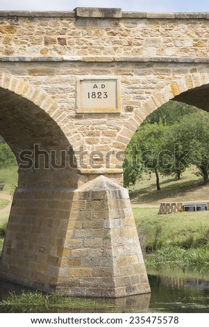 Historic building in heritage listed Richmond, Tasmania, oldest convict built stone bridge in Australia 1823, with mirror image in water of river beneath arches, tourist attraction close to Hobart. - stock photo