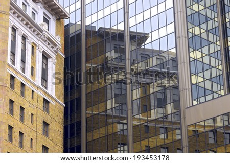 Historic building in Saint Paul reflected in modern glass high rise