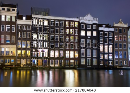 Historic buildings of old Amsterdam at night. - stock photo