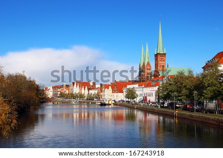 Historic buildings reflected in Trave river, old town of Lubeck, Germany - stock photo