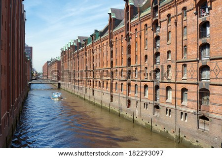 Historic canals among red brick storage facilities in the Speicherstadt harbor area of Hamburg, Germany.