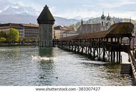 Historic city center of Lucerne with famous Chapel Bridge and Mount Pilatus summit in the evening with blue sky and clouds, Canton of Lucerne, Switzerland