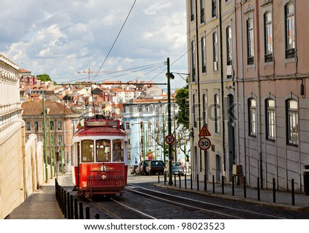historic classic red tram of Lisbon built partially of wood navigating, narrow, winding streets, Portugal