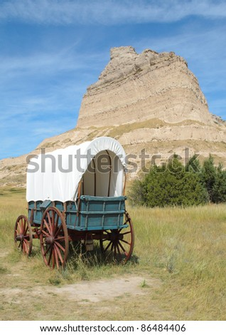 historic covered wagon next to Scotts Bluff National Monument - stock photo