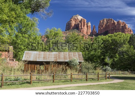 Historic Crescent Moon Ranch State Park in Sedona Arizona showing abandoned  ranch buildings, water mill and Cathedral Rocks in the background. - stock photo