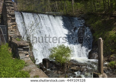 Historic dam on the Hockanum River below the Amerbelle, Hockanum and Dart's Stone Mills complex in Rockville, Connecticut. - stock photo