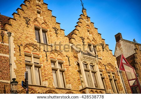 Historic facade of Bruges in Belgium / Beautiful old town of Bruges / Facade before blue sky - stock photo
