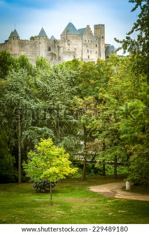 Historic Fortified City of Carcassonne in France towering over green alley with curved path. Medieval fortress under clear blue sky with greenery in foreground. Architecture and landmarks of Europe. - stock photo