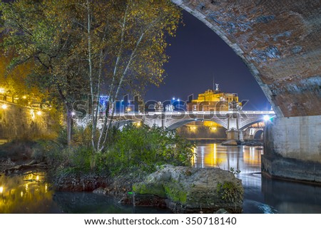 Historic fortress Castel Sant Angelo in Rome, Italy, wit the Angel's bridge, lit at night, seen from under the bridge on Tiber, with trees and bushes - stock photo
