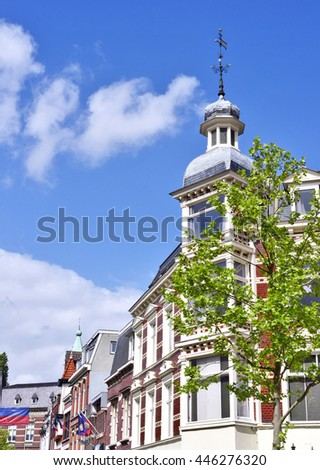 Historic house facade of the turn of the century, Netherlands. Old town on a sunny day with blue sky and fluffy clouds.