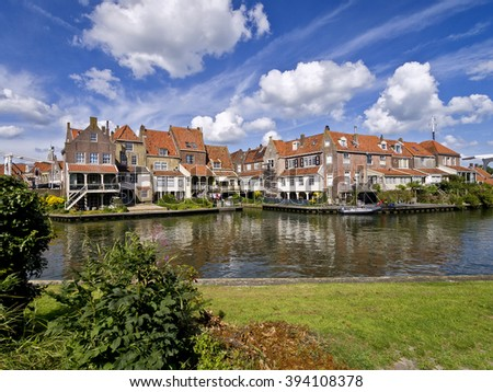 Historic houses in the historic Dutch fisherman's village of Enkhuizen, seen from across the water under a beautiful sky - stock photo