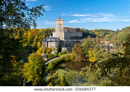 Historic medieval castle in the Czech Republic in autumn September, surrounded by forest and trees with colorful leaves.