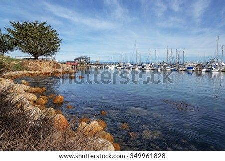 Historic Monterey Harbor and Marina; moored & anchored colorful sailboats, yachts, and speed boats. Located in the Monterey Bay National Marine Sanctuary, on California Central Coast, near Big Sur. - stock photo