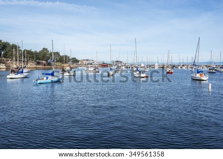 Historic Monterey Harbor and Marina; moored & anchored sailboats, yachts, and speed boats. Located in the Monterey Bay National Marine Sanctuary, on California Central Coast, near Big Sur. - stock photo
