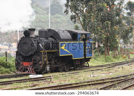 historic old vintage steam engine locomotive train moving down railroad track Nilgiri Mountain Railway Ooty India.  - stock photo