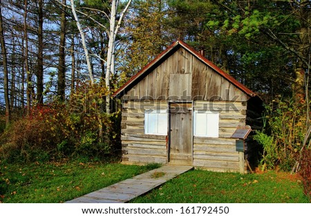 Historic one room log cabin, with fall forest in the background. Pt. Sanilac Historical Village. Pt. Sanilac, Michigan.  - stock photo