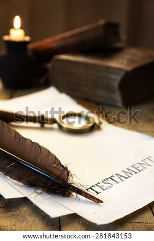 Historic parchment with text Testament, candle, feather and magnifier