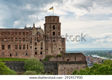 Historic Ruins of Heidelberg Castle with Waving Flag Overlooking Picturesque Town and Neckar River Below, Baden-Wurttemberg, Germany - stock photo