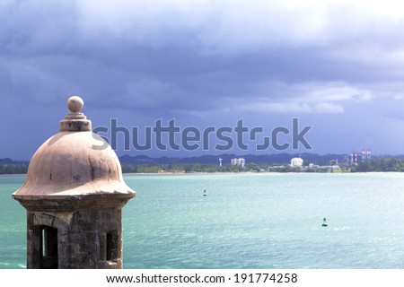Historic Spanish watchtower overlooking San Juan Bay with dramatic stormy sky - stock photo