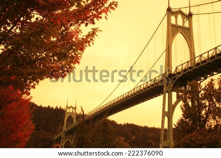 Historic St. John's Bridge in Fall in Portland, OR.  Taken from Cathedral Park.  The St. John's Bridge sits over the Willamette River.  - stock photo