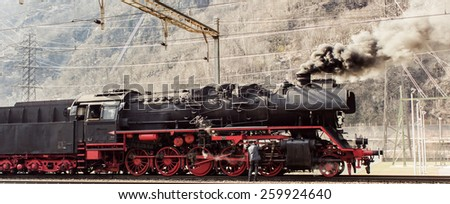 historic steam train in the snow in the mountains of Switzerland - stock photo