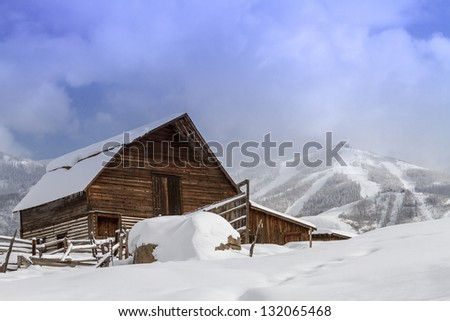 Historic Steamboat Springs barn on snowy hill with ski area lifts and slopes in background - stock photo