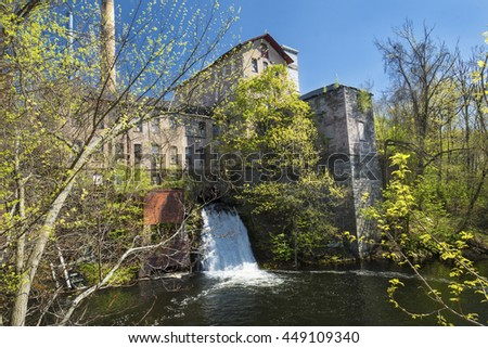 Historic, 19th century mill, known as Dart's Stone Mill, with water power sluice on the Hockanum River in Rockville, Connecticut. - stock photo