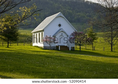 Historic white clapboard country church nestles on a hillside in the Virginia mountains. - stock photo