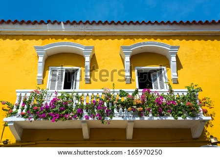 Historic yellow and white balcony in Cartagena, Colombia with colorful flowers - stock photo